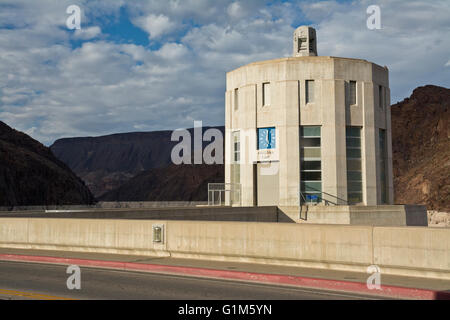 Roadway over Hoover dam and top of water intake tower on Arizona side with clock showing Arizona time. - Stock Photo
