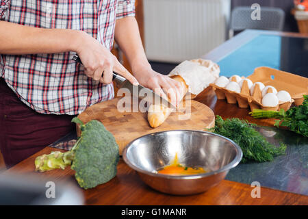 Closeup of young woman cutting baguette and cooking on the kitchen - Stock Photo
