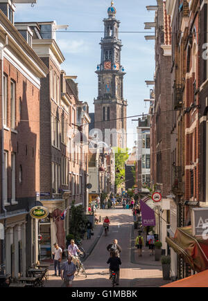 Amsterdam Jordaan. Streets and bridge in the Jordaan district with cyclists cycling in the sun. Westertoren in the - Stock Photo
