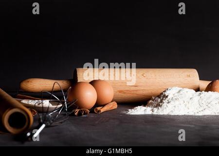 Ingredients like eggs, flour, cinnamon, anise, rolling pin, paper on blackboard - Stock Photo