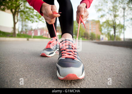 Sporty woman tying shoelace on running shoes before practice. Female athlete preparing for jogging outdoors - Stock Photo