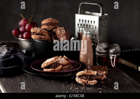 Italian maroni cookies on the plate and bowl with grapes, chocolate milkshakes, cloth, notebook on dark old wooden - Stock Photo