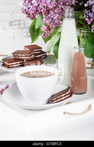 Cup of coffee and few bottles of milk and chocolate miklshakes on a white tray with lilac flowers on white shutters - Stock Photo