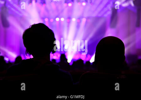 Unrecognizable people watching a beautiful laser show with multicolored lights - Stock Photo