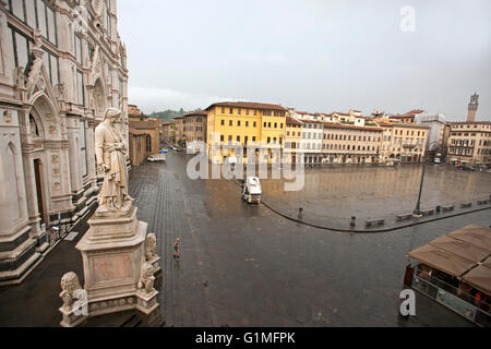 marble statue of Dante Alighieri looks down into rain drenched Piazza di Santa Croce, Florence, Tuscany, Italy - Stock Photo