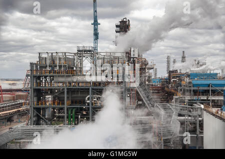 Chemical plant for production of ammonia and nitrogen fertilization on day time. The steam from the cooling system - Stock Photo