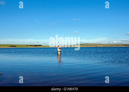 fly fishing on Colliford reservoir lake Bodmin Moor Cornwall lone man casting with rod on still lake blue sky - Stock Photo