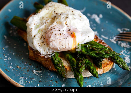 Toasted sourdough bread with grilled asparagus, poached egg and parmesan - Stock Photo