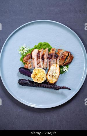 Lamb leg fillet with wild garlic puree, roast garlic bulb and jerusalem artichoke - Stock Photo