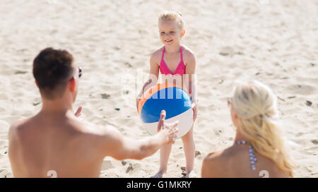happy family playing with inflatable ball on beach - Stock Photo