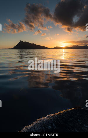 Sunset behind Bream Head, seen from a boat sailing north. North Island, New Zealand - Stock Photo