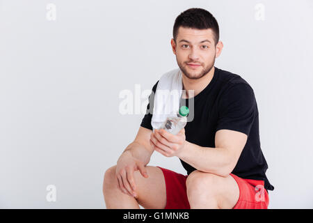 Young sports man with towel holding bottle with water isolated on a white background - Stock Photo