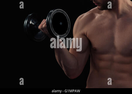 Cropped image of a muscular man workout with dumbbell - Stock Photo