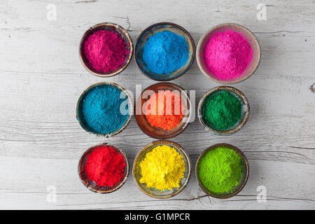 Colorful Holi powder in cups on white rustic wooden table. Top view with copy space. - Stock Photo