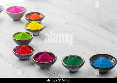 Bright and colorful dyed powder in ceramic cups on white rustic wooden table. - Stock Photo