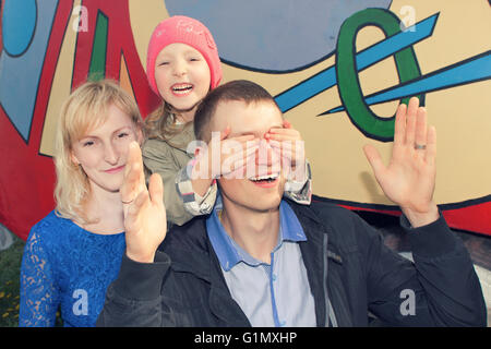 Mother father daughter playing hide and seek - Stock Photo