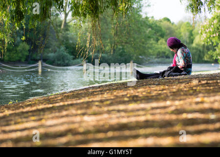 LONDON, UK - MAY 16 2016  Lady painting by lake in Regent's Park. An artist in purple beret sketching in tranquil - Stock Photo