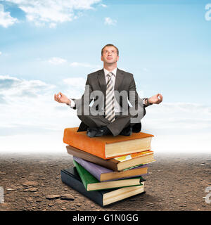 Man sitting on pile of books and meditating - Stock Photo