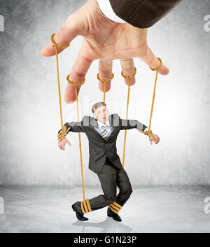 Businessman hanging on strings like marionette - Stock Photo