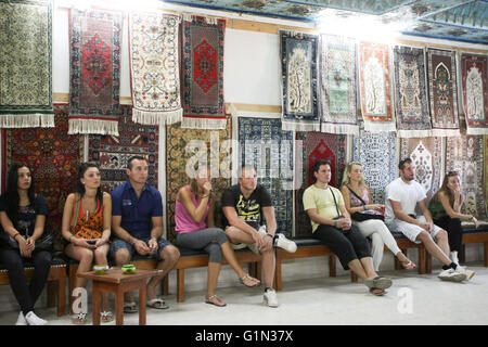 A tourist group in an ancient shop with old craft production of silk and wool in Kairouan, Tunisia. - Stock Photo