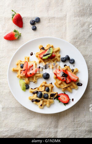 belgian waffles with strawberries, blueberries and kiwis, food top view - Stock Photo