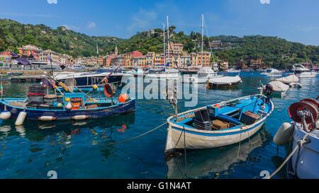 Portofino, Genoa Province, Liguria, Italian Riviera, Italy.  Boats in the harbour with the village behind. - Stock Photo