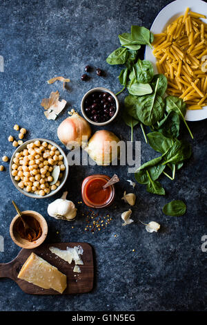 Ingredients for chickpea spinach pasta with olives (gluten-free quinoa penne). - Stock Photo