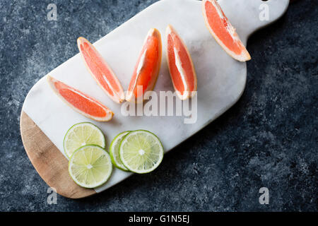 Sliced grapefruits and limes on a chopping board. - Stock Photo