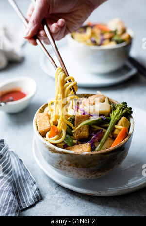 Curried noodles with crispy tofu & winter vegetables, gluten-free and vegan. - Stock Photo