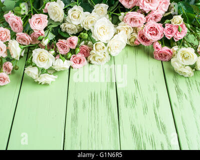 Delicate fresh roses on the green wooden background. - Stock Photo