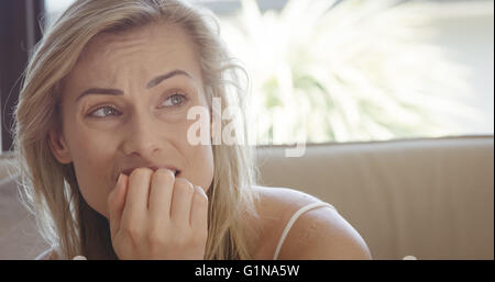 Stressful woman sitting on sofa - Stock Photo