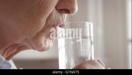 Senior woman drinking water glass - Stock Photo