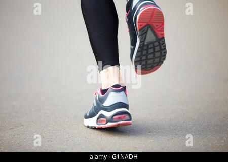 Legs of young female model running in park during everyday practice. Fitness woman in training shoes jogging outdoors - Stock Photo