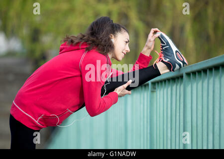 Portrait of sporty smiling woman doing hamstring stretch in park after jogging. Female athlete runner getting ready - Stock Photo