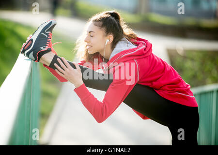 Profile portrait of sporty woman doing hamstring stretch in park after jogging. Female athlete runner getting ready - Stock Photo