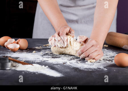 Making of cookies with ingredients like eggs, flour, cinnamon, anise, rolling pin, paper on blackboard - Stock Photo