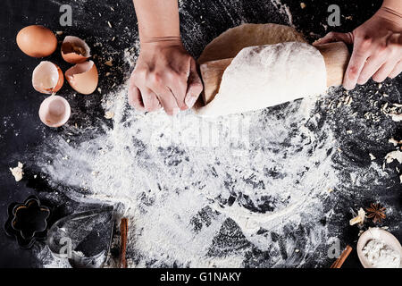 Making of cookies with ingredients like eggs, flour, cinnamon, anise, rolling pin, paper on blackboard from the - Stock Photo