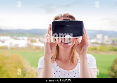 Woman wearing virtual reality goggles standing in a kitchen - Stock Photo