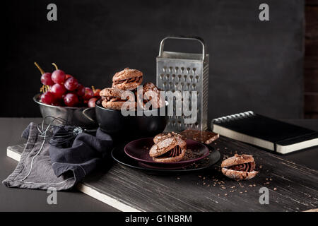 Italian maroni cookies on the plate and bowl with grapes, cloth, notebook on dark old wooden background - Stock Photo
