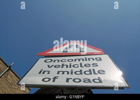 british road sign for narrowing road and stating oncoming vehicles in middle of road - Stock Photo