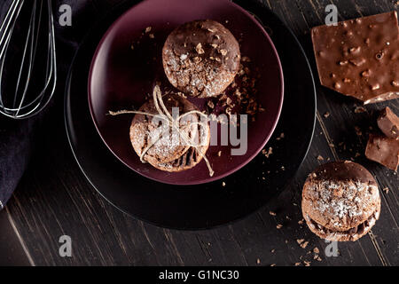 Italian maroni cookies on the plate and chocolate milkshakes, cloth, notebook on dark old wooden background, top - Stock Photo