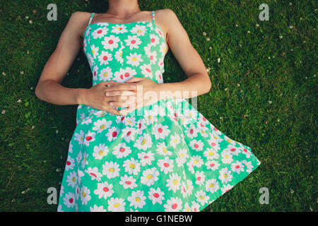 A young woman wearing a flowery dress is lying on the grass in summer - Stock Photo