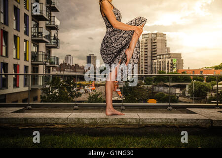 A young woman wearing a dress is raising her leg as she is standing on a roof top - Stock Photo