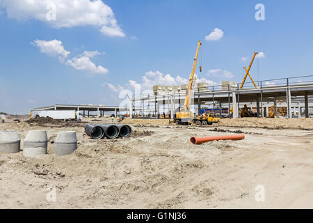 Mobile crane is loading cargo. View on construction site with machinery, people at work. - Stock Photo