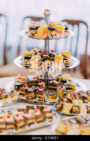 Collection of delicious assorted mini dessert standing on a table in restaurant - Stock Photo