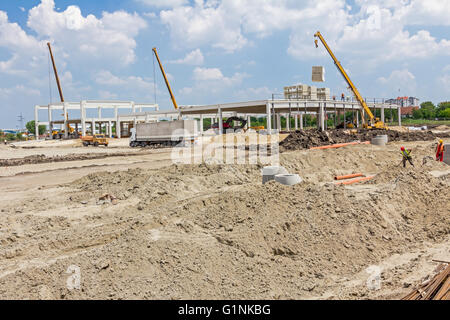 Mobile crane is loading cargo. View on construction site with machinery, people at work. Landscape transform into - Stock Photo