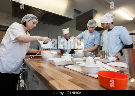 International school class learns how to cook and bake in the training kitchen. - Stock Photo