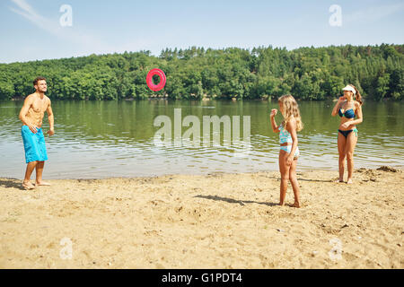Family and daughter playing on the shore with a frisbee in summer - Stock Photo