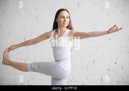 Portrait of attractive cheerful young woman working out indoors. Beautiful model doing exercises on blue mat in - Stock Photo