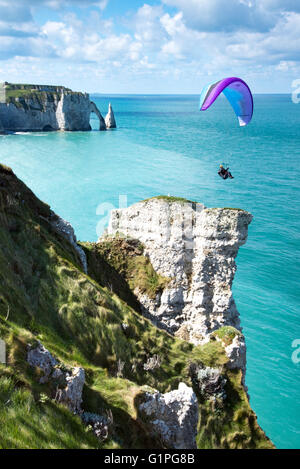Paraglider flying over Falaise d'Amont cliff, with Porte d'Aval arch and Aiguille needle in background, Etretat, - Stock Photo